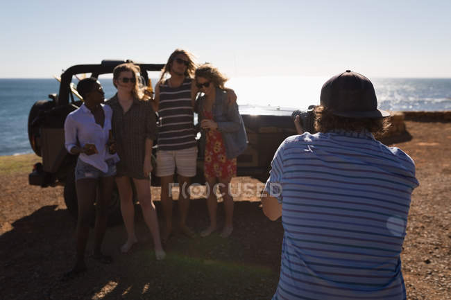 Male friend clicking photos of friends with camera in the beach — Stock Photo