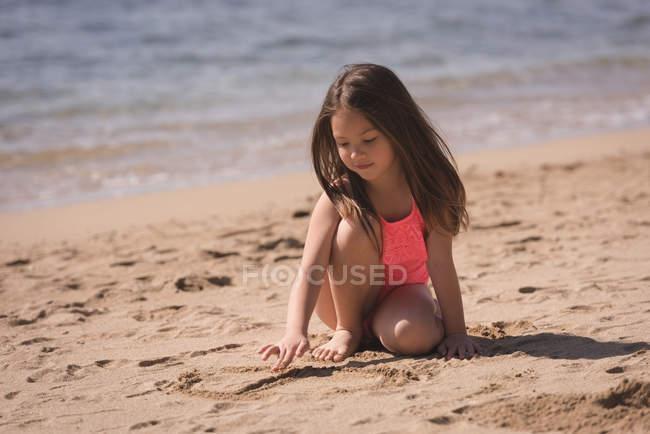 Гарна дівчинка, грає на піску на пляжі — стокове фото
