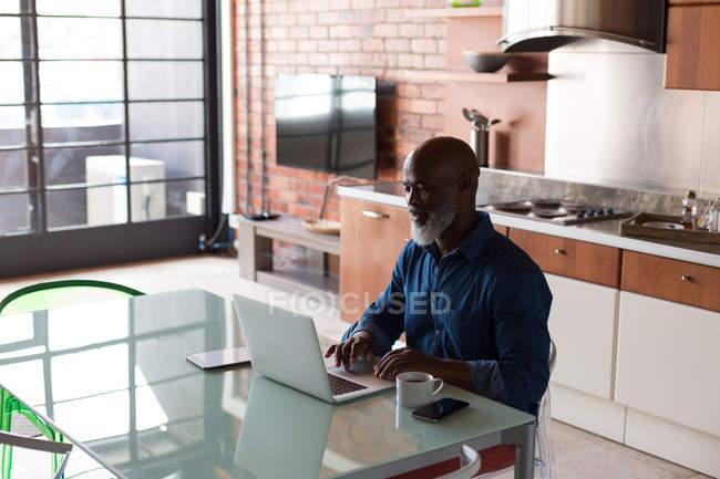 Пожилой мужчина использует ноутбук на кухне дома — стоковое фото