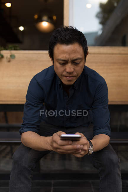 Концентрат бизнесмен, используя мобильный телефон в кафе — стоковое фото