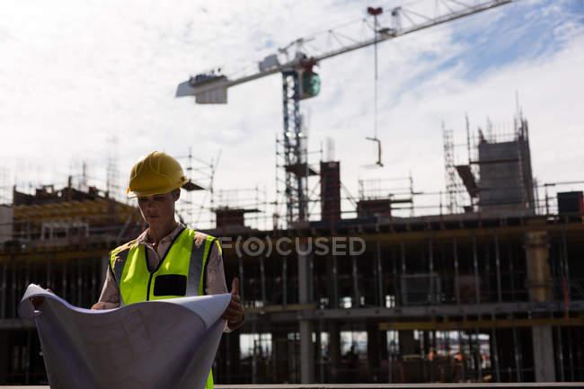 Архитектор-женщина проверяет чертежи на стройке — стоковое фото