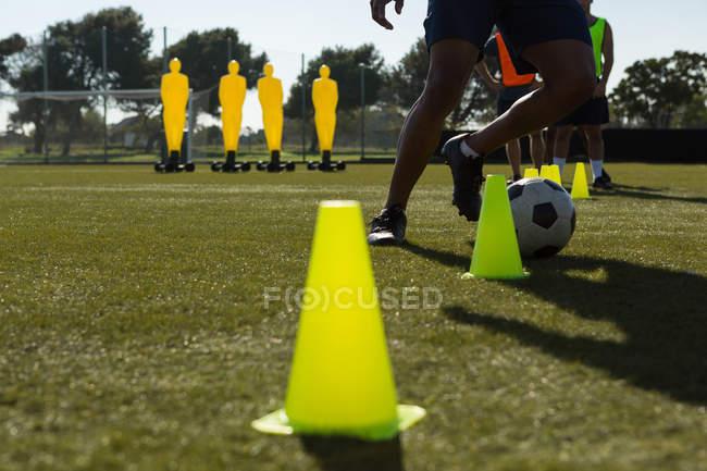 Futbolista driblando la bola a través de conos en el campo de los deportes - foto de stock