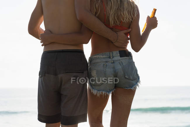 Rear view of couple standing with arms around in the beach — Stock Photo