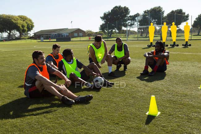 Jugadores de fútbol relajantes en el campo de los deportes - foto de stock