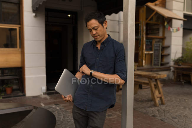Standing businessman with laptop checking his smartwatch — Stock Photo