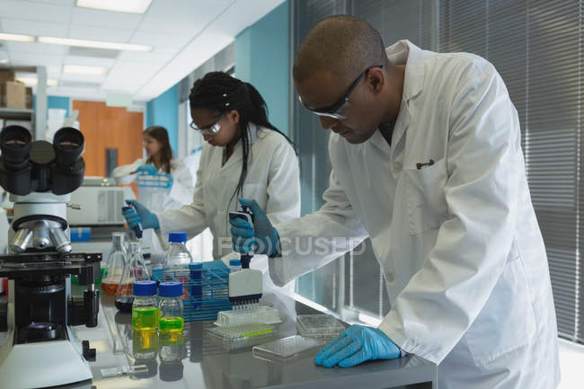 Side view of two scientists doing experiment in lab — Stock Photo