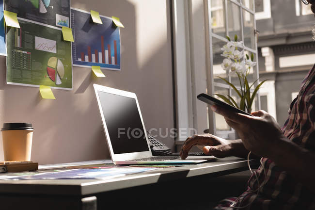 Senior graphic designer using laptop and mobile phone in office — Stock Photo