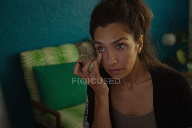Beautiful female video blogger applying eye liner at home — Stock Photo