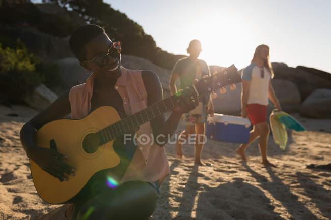 Femme jouant de la guitare à la plage par une journée ensoleillée — Photo de stock