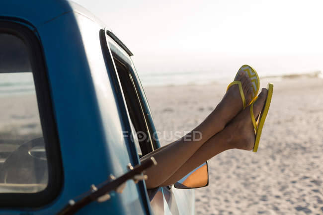 Woman relaxing with feet up in a pickup truck at beach — Stock Photo