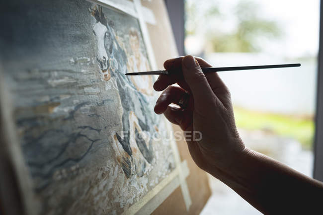 Hand of female artist painting picture on canvas at home — Stock Photo