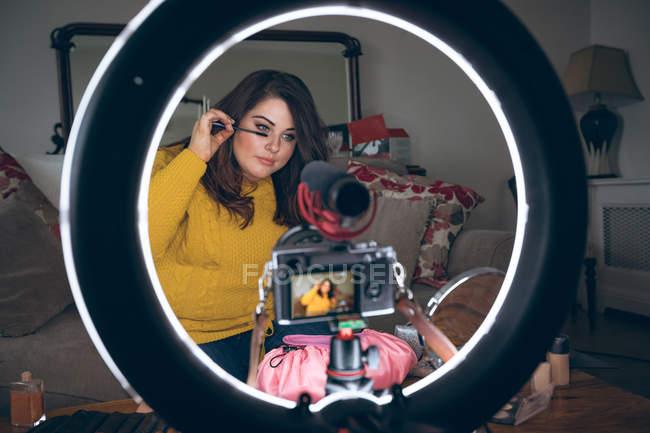 Beautiful woman applying eye shadow at home — Stock Photo