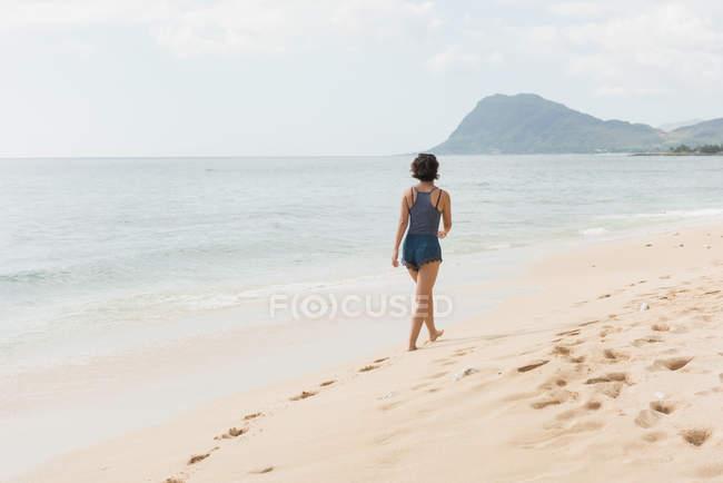 Vista posteriore della donna che cammina in spiaggia in una giornata di sole — Foto stock