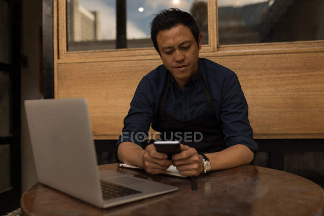 Businessman using mobile phone with laptop on table in the cafe — Stock Photo