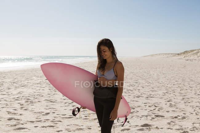 Surfista femminile in piedi con il surf in spiaggia in una giornata di sole — Foto stock