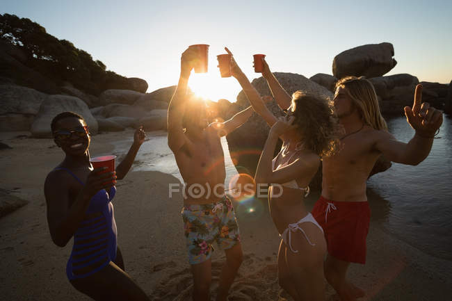Group of friends having fun in the beach at dusk — Stock Photo