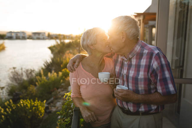 Senior couple kissing each other in the balcony at home — Stock Photo