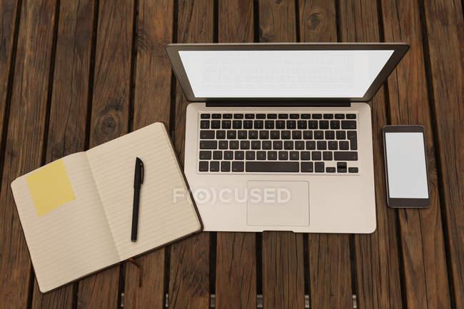Ordenador portátil, diario, pluma y teléfono móvil en la mesa en el café - foto de stock
