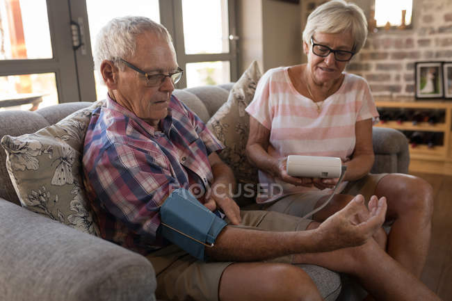 Senior couple checking blood pressure with sphygmomanometer in living room at home — Stock Photo