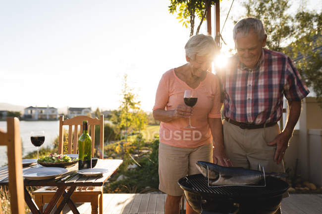 Älteres Paar Kochen Fisch am Grill im Garten — Stockfoto