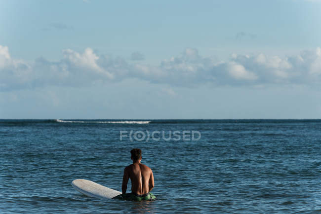 Male surfer surfing with surfboard in the sea on a sunny day — Stock Photo
