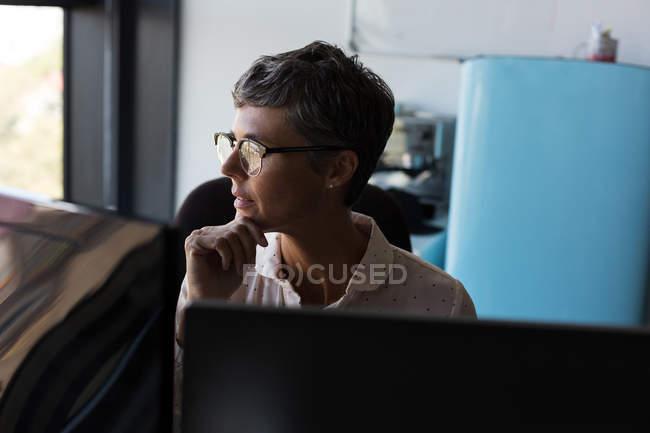 Задумчивая зрелая деловая женщина смотрит в сторону в офисе — стоковое фото