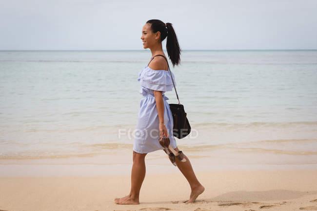 Lächelnde schöne Frau, die am Strand auf Sand läuft — Stockfoto