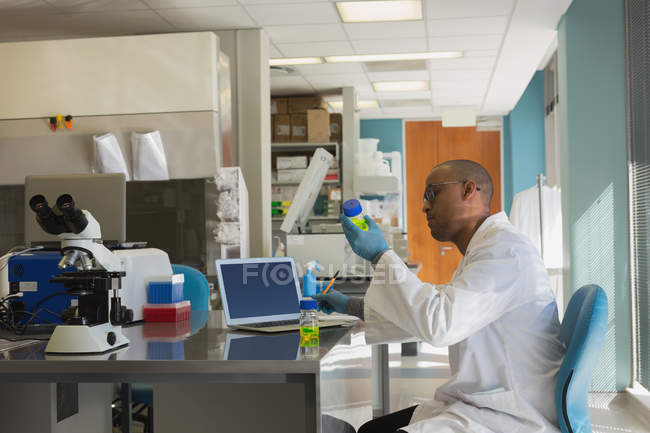 Scientifique vérifiant une solution chimique en laboratoire — Photo de stock