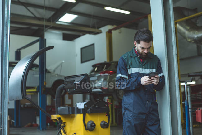 Mechanic using mobile phone in repair garage — Stock Photo