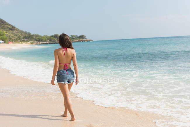 Вид сзади на женщину, идущую по пляжу в солнечный день — стоковое фото