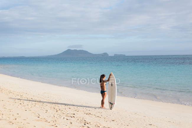 Woman standing with surfboard in the beach on a sunny day — Stock Photo