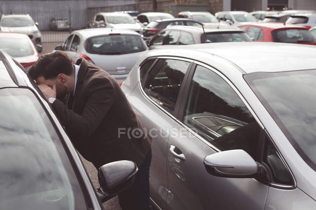 Salesman peeping through car window outside the showroom — Stock Photo