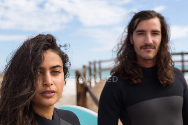 Portrait of surfer couple standing together in the beach — Stock Photo