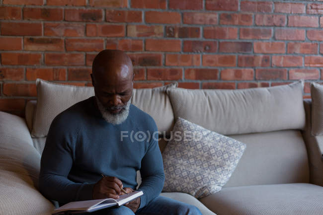 Senior man writing in a diary at home — Stock Photo