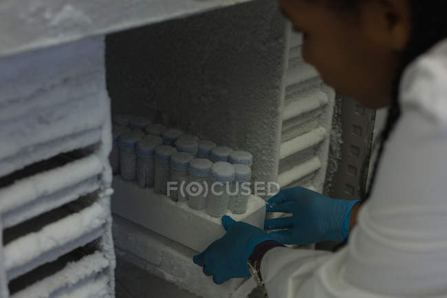 Scientist looking at test tubes in lab — Photo de stock
