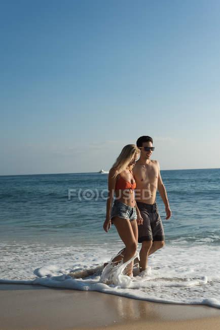 Coppie che camminano insieme, mano nella mano in spiaggia — Foto stock