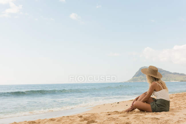 Woman in hat relaxing in the beach on a sunny day — Stock Photo
