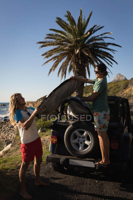 Amis masculins enlever la planche de surf de la jeep dans la plage — Photo de stock