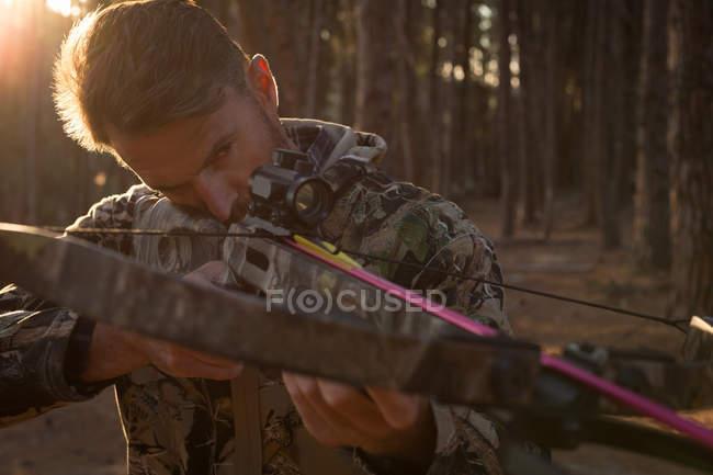 Uomo che punta il tiro con l'arco nella foresta con arco e freccia in una giornata di sole — Foto stock