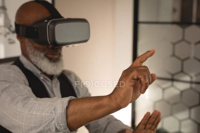 Designer gráfico sênior usando headset de realidade virtual no escritório — Fotografia de Stock