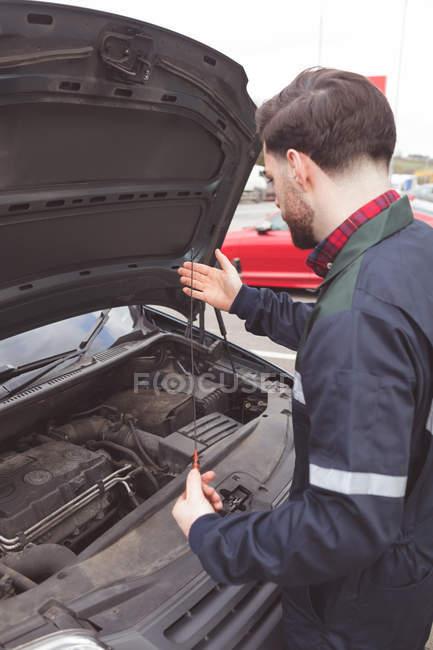 Mecánico masculino servicio de coches en el garaje de reparación - foto de stock