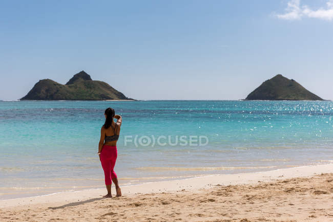 Rear view of woman standing in the beach on a sunny day — Stock Photo