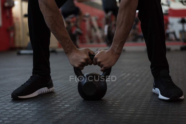 Athlete exercising with kettlebell in gym — Stock Photo