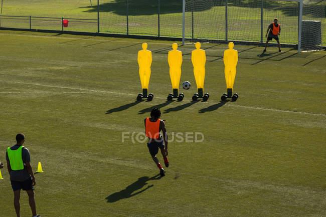 Гравці практикуючих футбол в поле у сонячний день — стокове фото