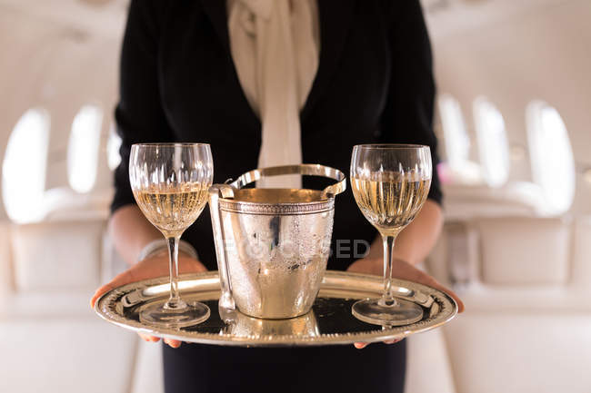 Mid section of flight attendant serving glasses of champagne in private jet — Stock Photo