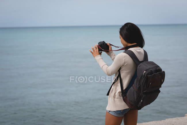 Visão traseira da mulher clicando foto do mar com câmera digital na praia — Fotografia de Stock