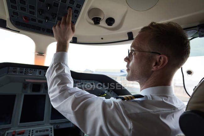 Male pilot pushing button in private cockpit — Stock Photo