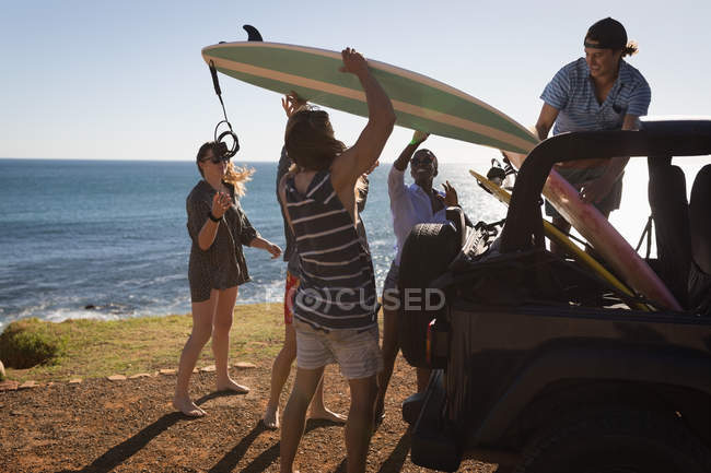 Group of friends removing surfboard from jeep in the beach — Stock Photo