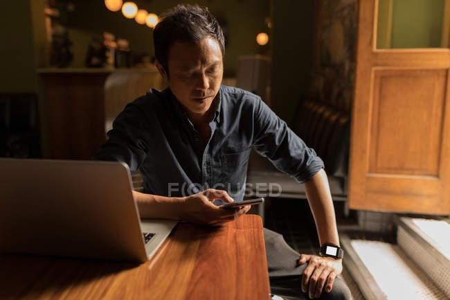 Концентрированные бизнесмен, с помощью мобильного телефона в кафе — стоковое фото