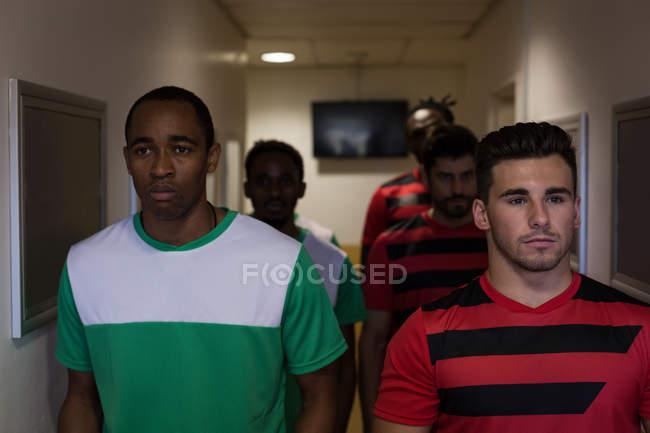 Vista frontal de jugadores de fútbol dejando el vestidor - foto de stock
